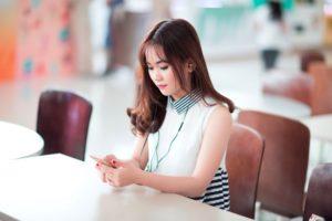 スマートフォンでリスニングをする女性のイメージ