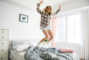 ベッドから跳ね起きる女性