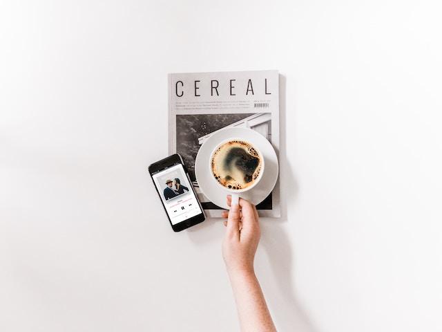 雑誌の上のコーヒーとスマートフォン