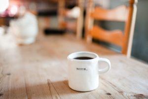 beginと書かれたマグカップに入ったコーヒー